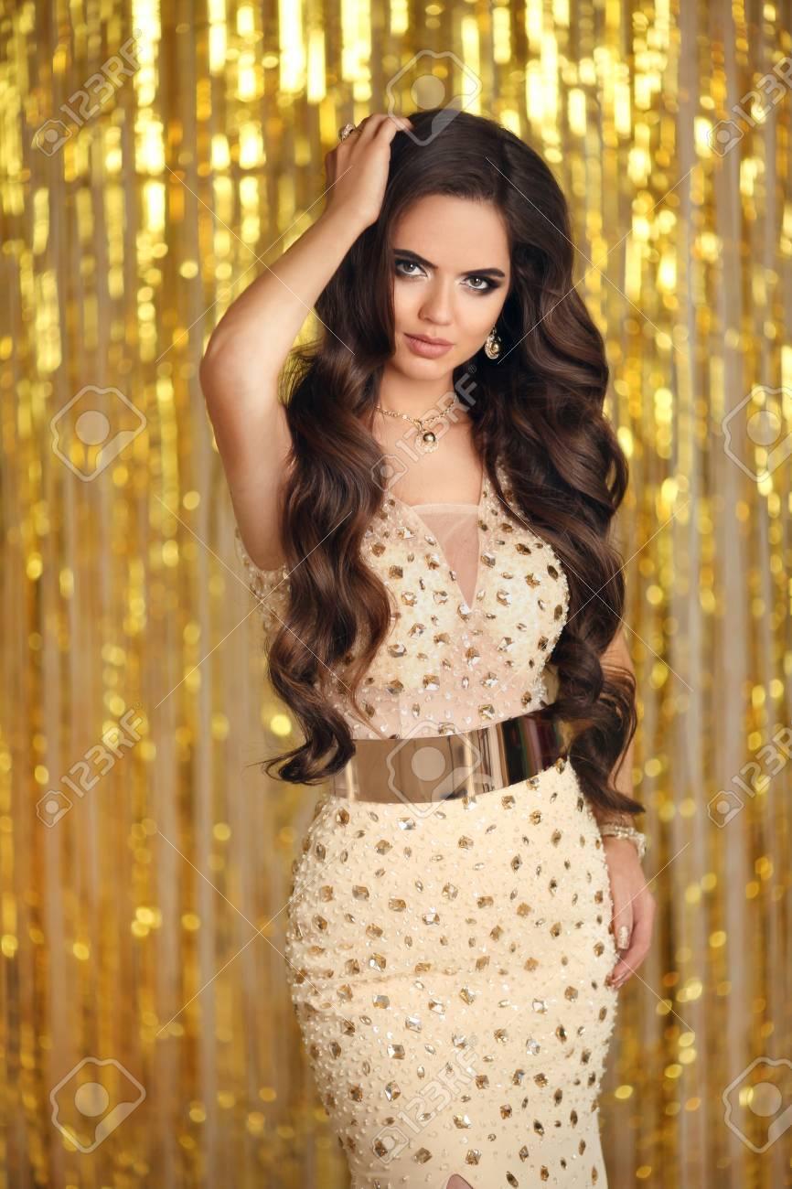 9d8ec3fc673 Brune élégante En Robe De Soirée Dorée. Style Glamour De La Mode. Maquillage  De Beauté Et Coiffure Ondulée. Belle Femme Souriante Avec Style De Cheveux  ...