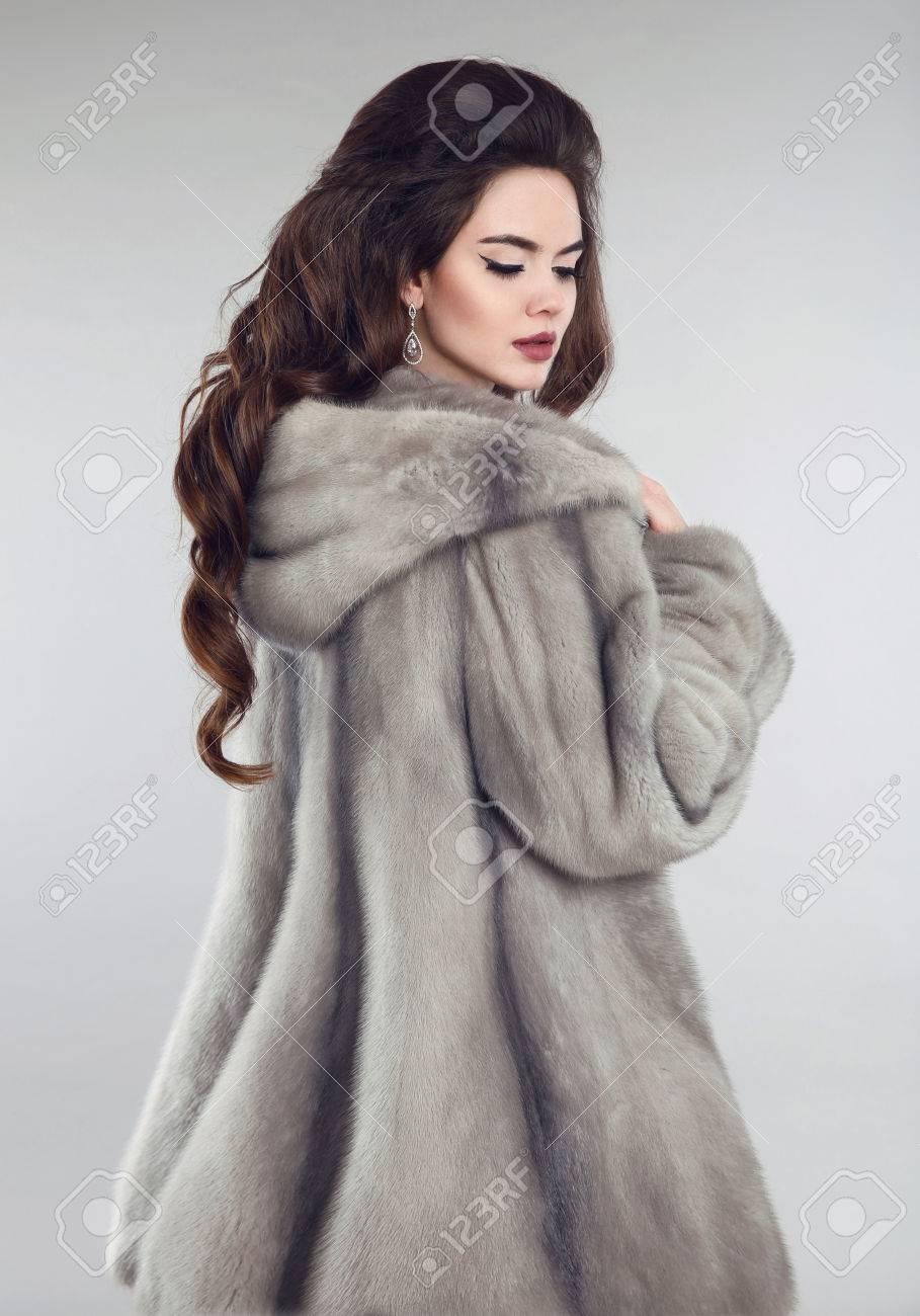 d8e413de4799d Fashionable woman in mink fur coat over studio gray background. Winter  portrait of brunette girl