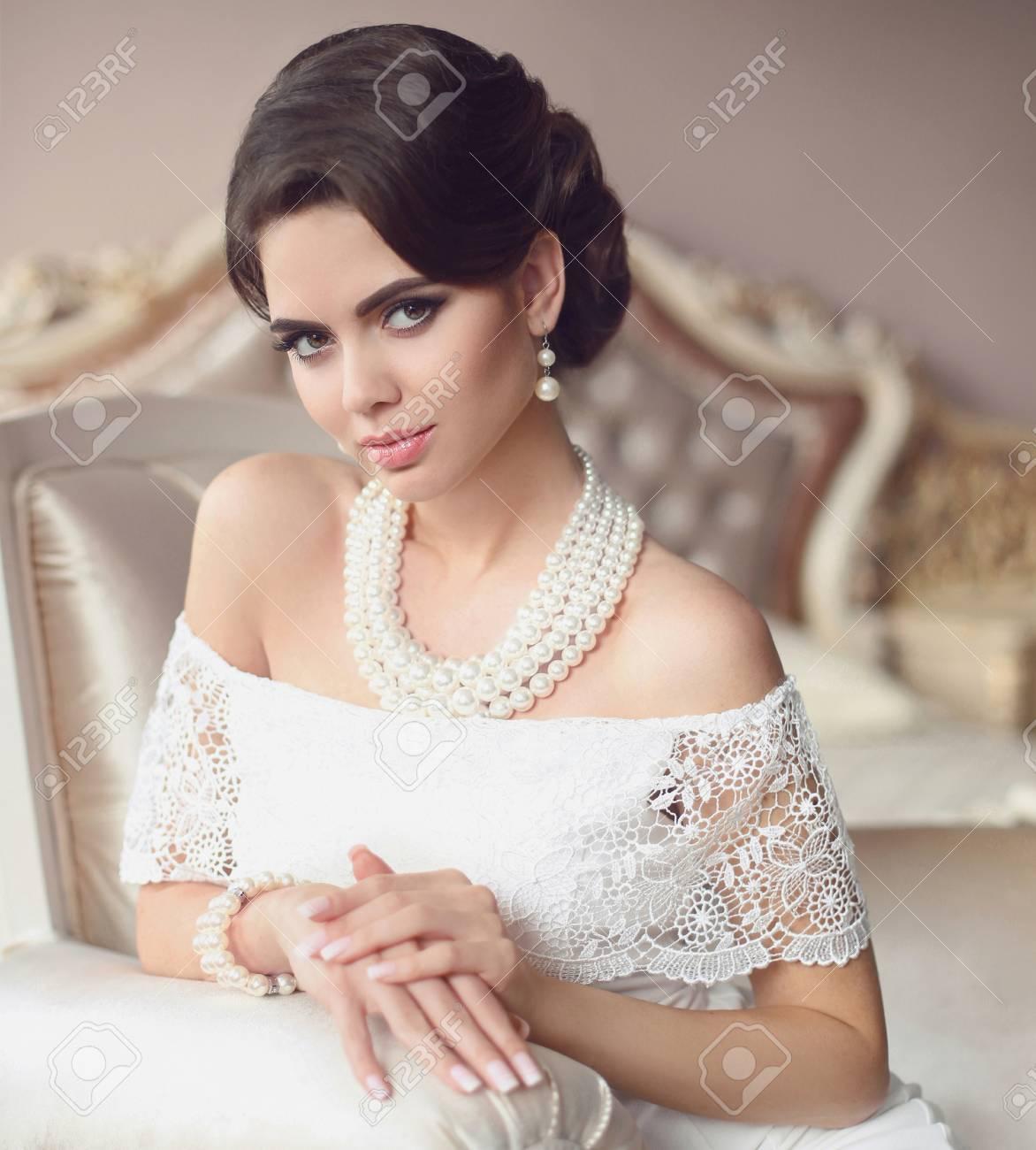 Hermosa Morena, Elegante Retrato De Mujer. Conjunto De Joyas De Perlas De  Moda. Señora Retra Con Maquillaje, Peinado Ondulado En Vestido Sexy Blanco  Posando En La Cama Moderna En El Interior De