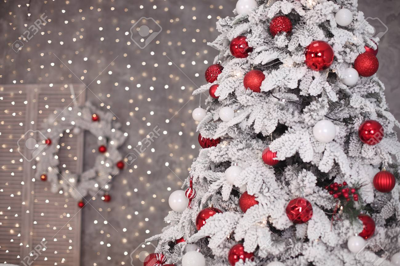 Snowy Christmas Tree With Red Gifts Before Bokeh Lights And Wreath