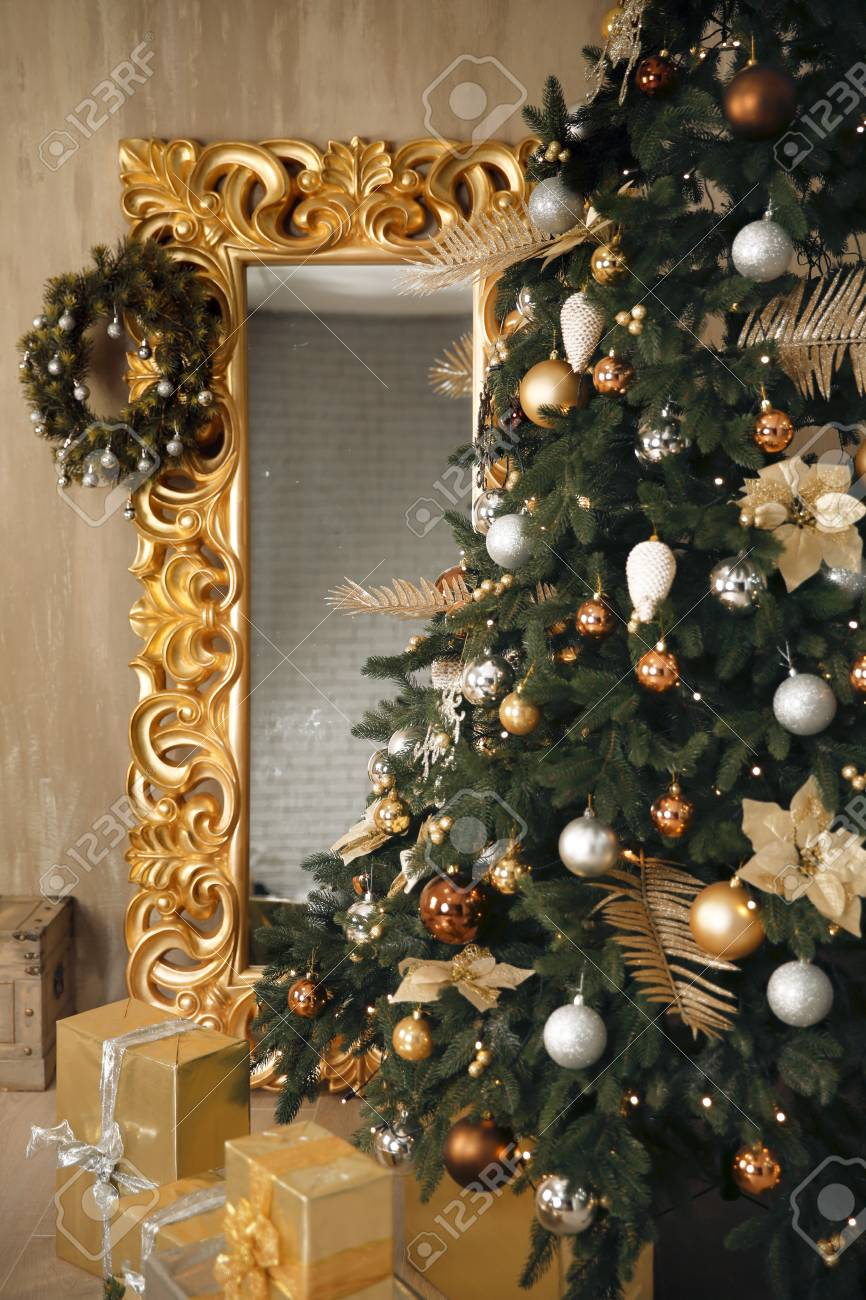 closeup of christmas tree decoration with wreath on golden frame mirror leaning on wall stock photo