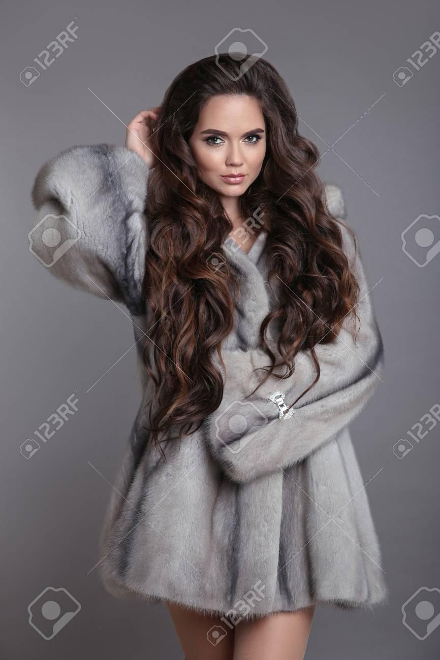 Elegant woman in mink fur coat isolated on gray studio background. Brunette Girl in Luxury Winter outerwear. Stock Photo - 114244969