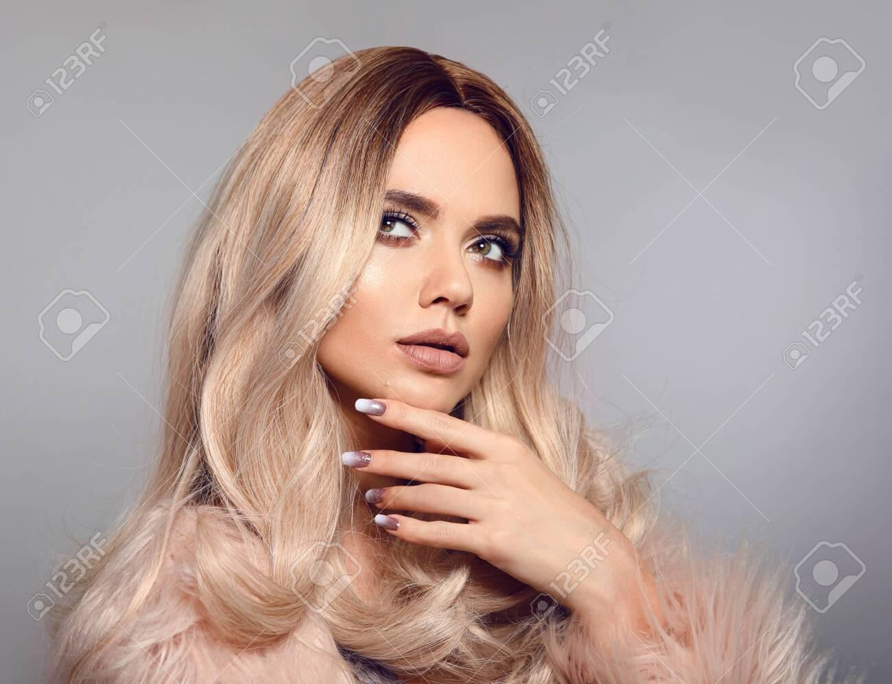 fe535f487 Blonde woman in glamorous fur coat posing in studio. Ombre blond..