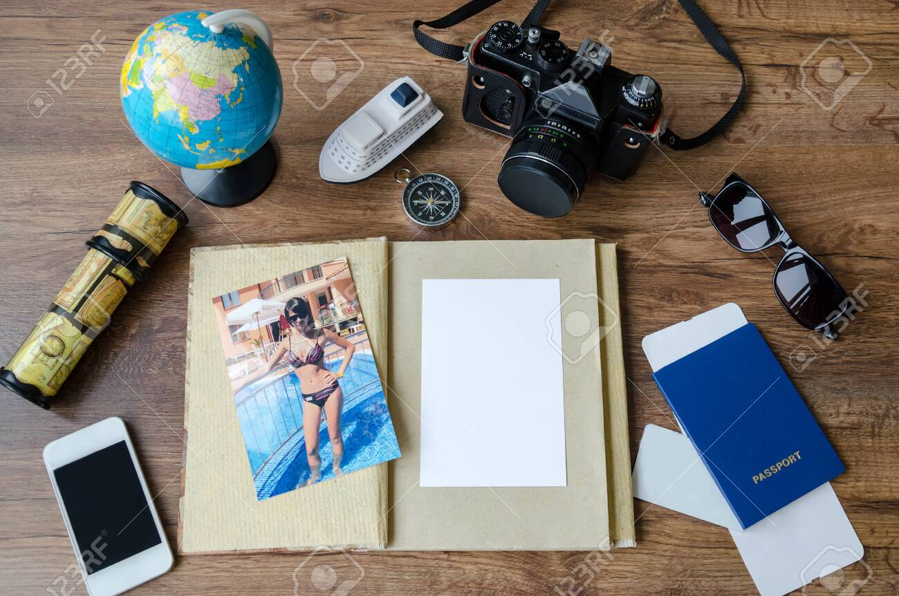 Notepad, credit cards, passport, ticket, luggage, phone and compass on a wooden background, set for travel planning - 140127032