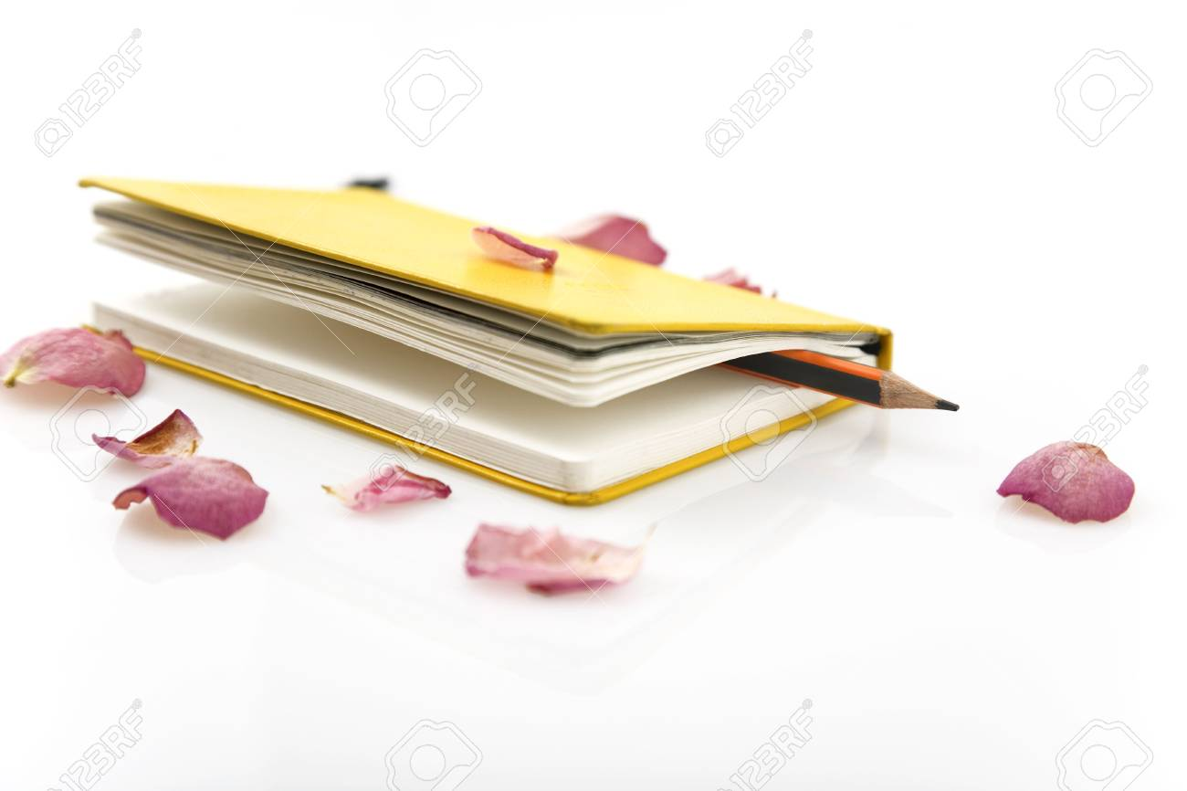 yellow notebook, pencil and rose petals isolated on white Stock Photo - 6675030