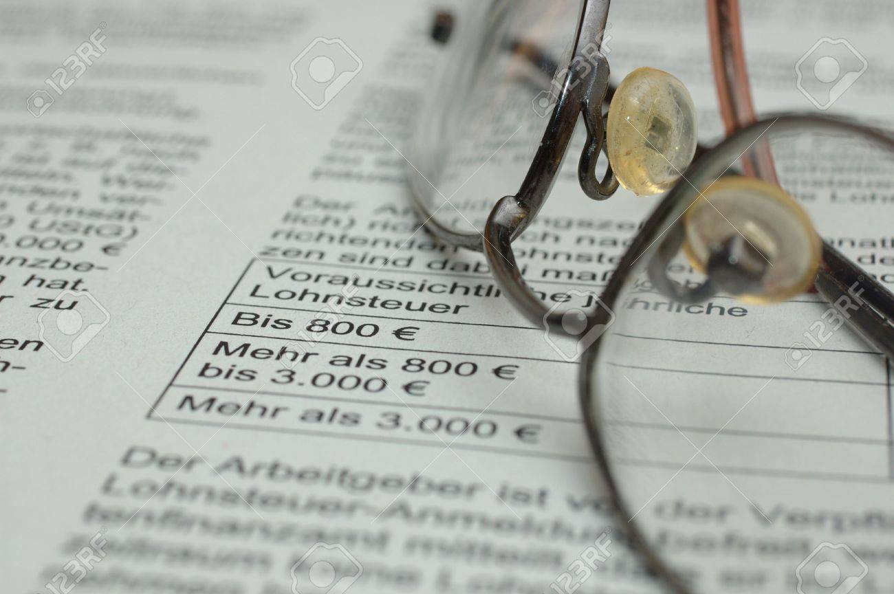 Glasses Lying On Business Report With German Text And Euro Symbol