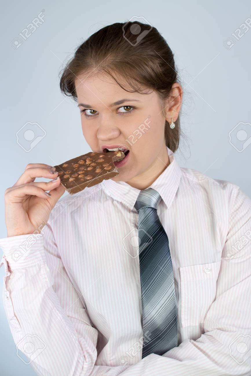 9cc47ff63ed 스톡 콘텐츠 - 젊은 비즈니스 여자 입고 비즈니스 셔츠와 넥타이 들고 초콜릿을 물고