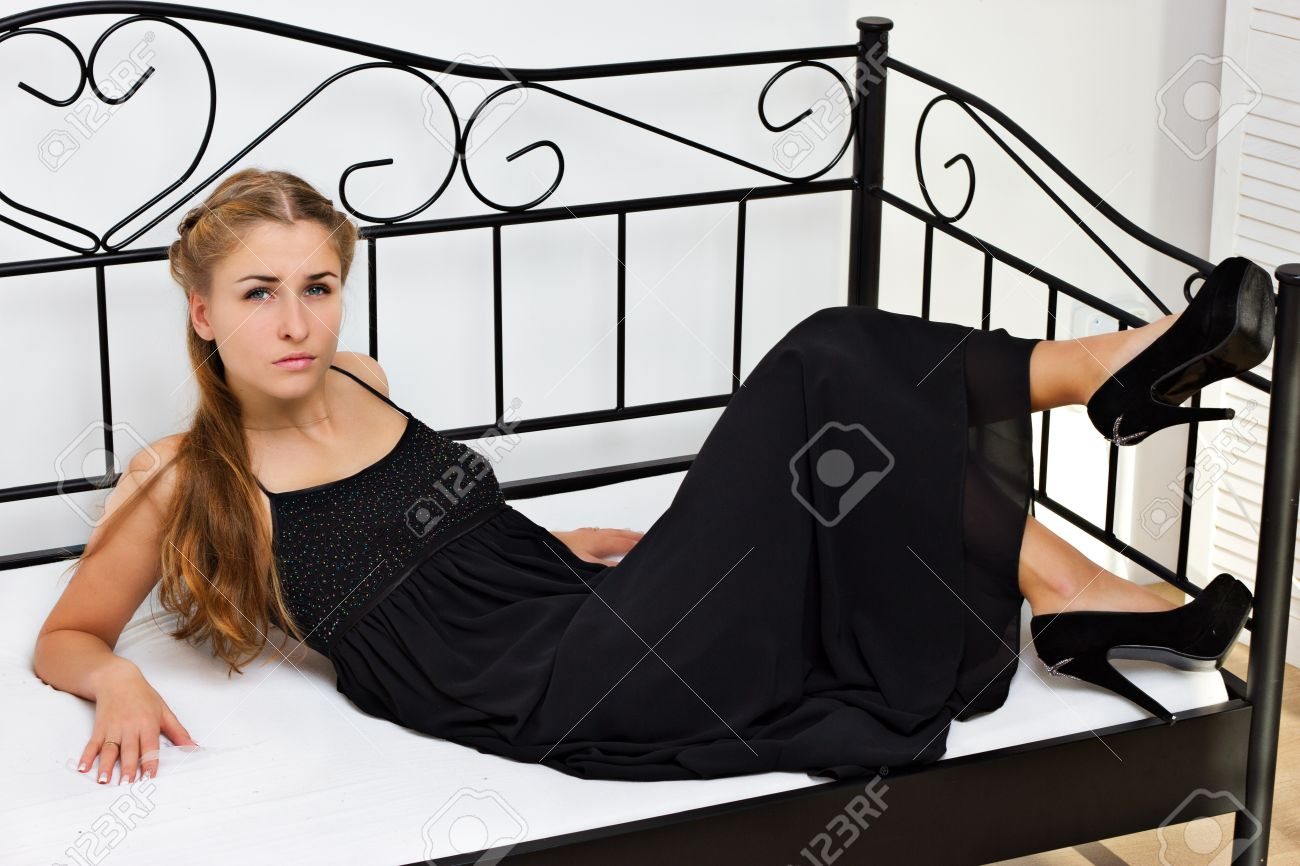 Girl in black dress shoes with high heels lying on the bed in the studio shooting Stock Photo - 12004974