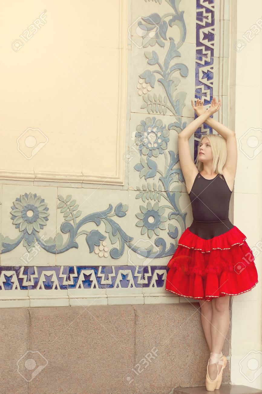 Ballerina on tiptoe with arms raised in pointe in red-black suit standing near the wall with ornament Stock Photo - 15646920