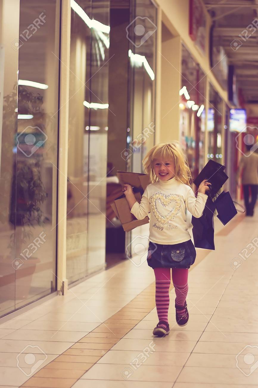 Blonde girl 3 years old in bright clothes running around the store with shopping Stock Photo - 15646899