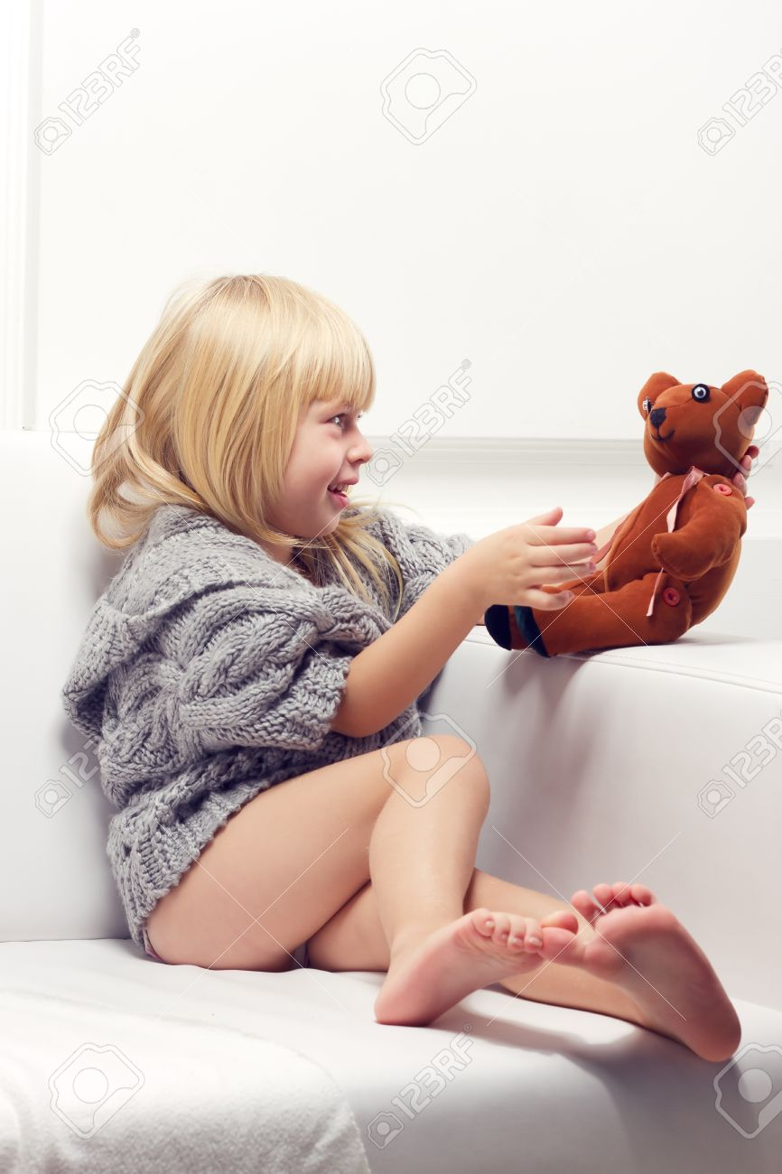 Little girl with bear on white sofa Stock Photo - 16409581