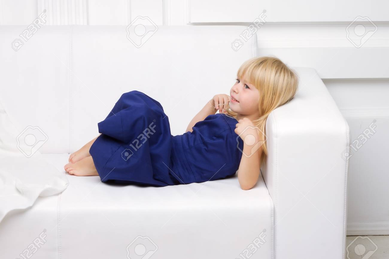 3 years old girl is in a blue dress on a white sofa Stock Photo - 16466634