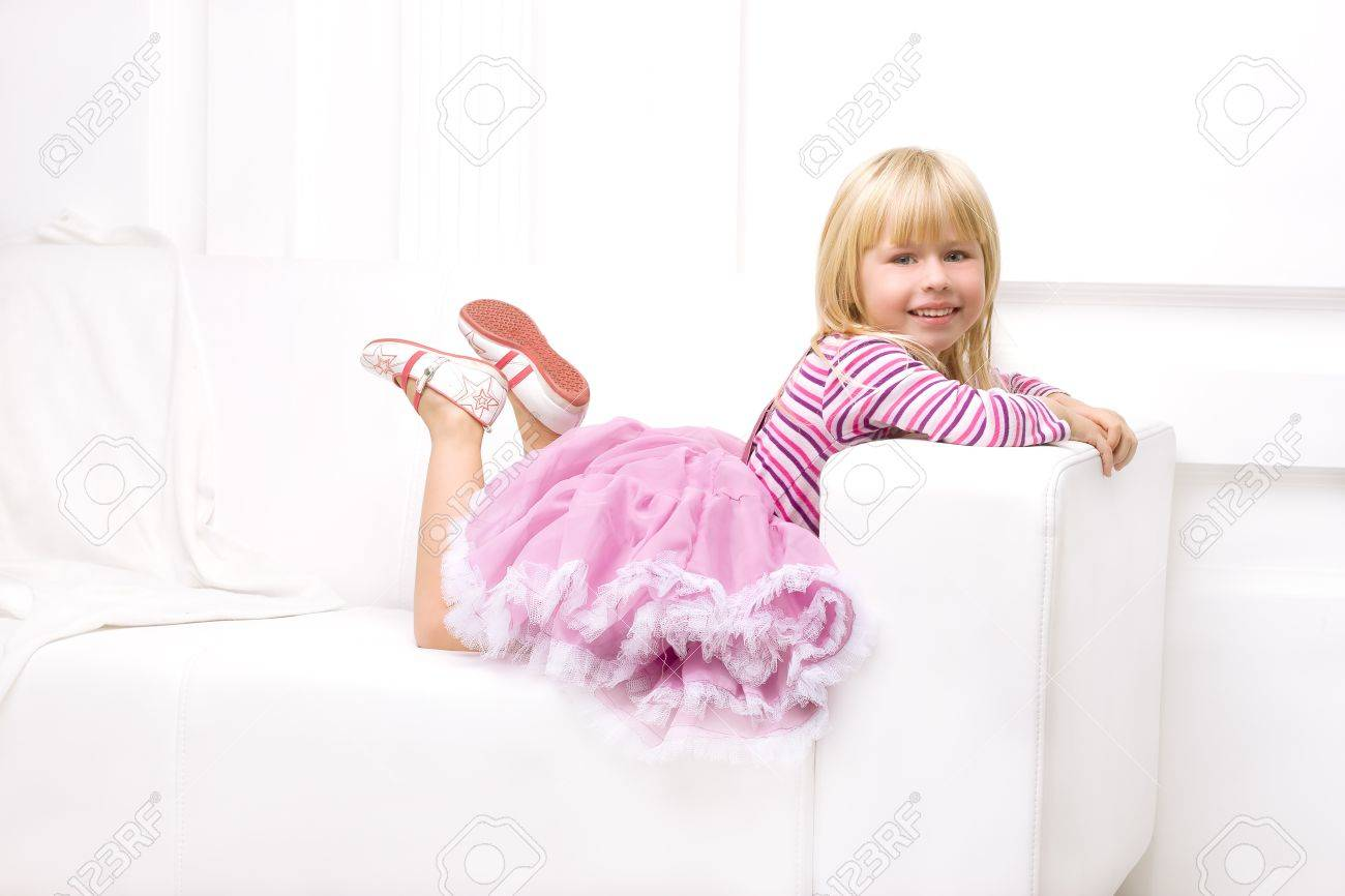 girl in a pink dress lying on a white sofa Stock Photo - 18346933