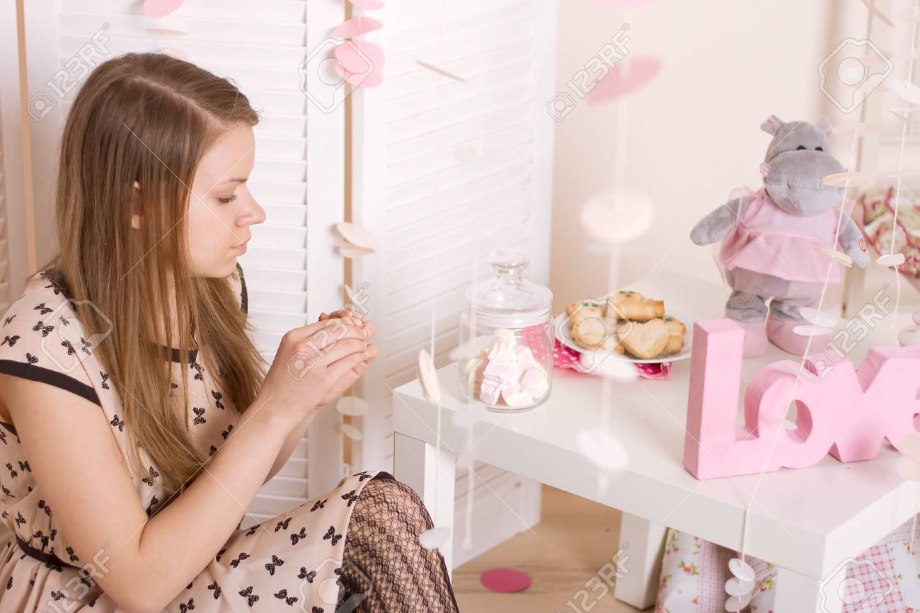 The girl at the table with decorations holding a jar of marshmallow Stock Photo - 19182064