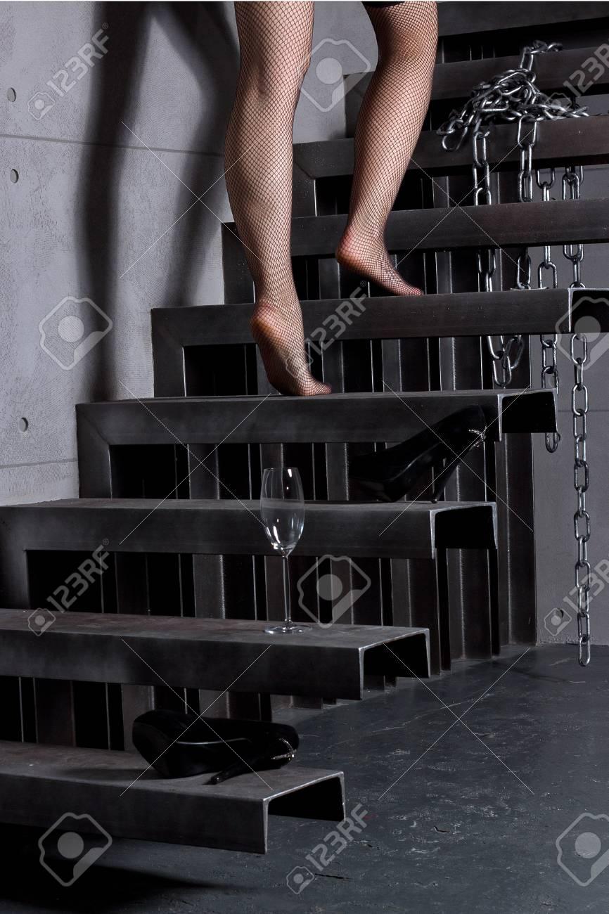 b9b0aca01 Falda de la mujer subiendo las escaleras en su casa, la celebración de  vidrio