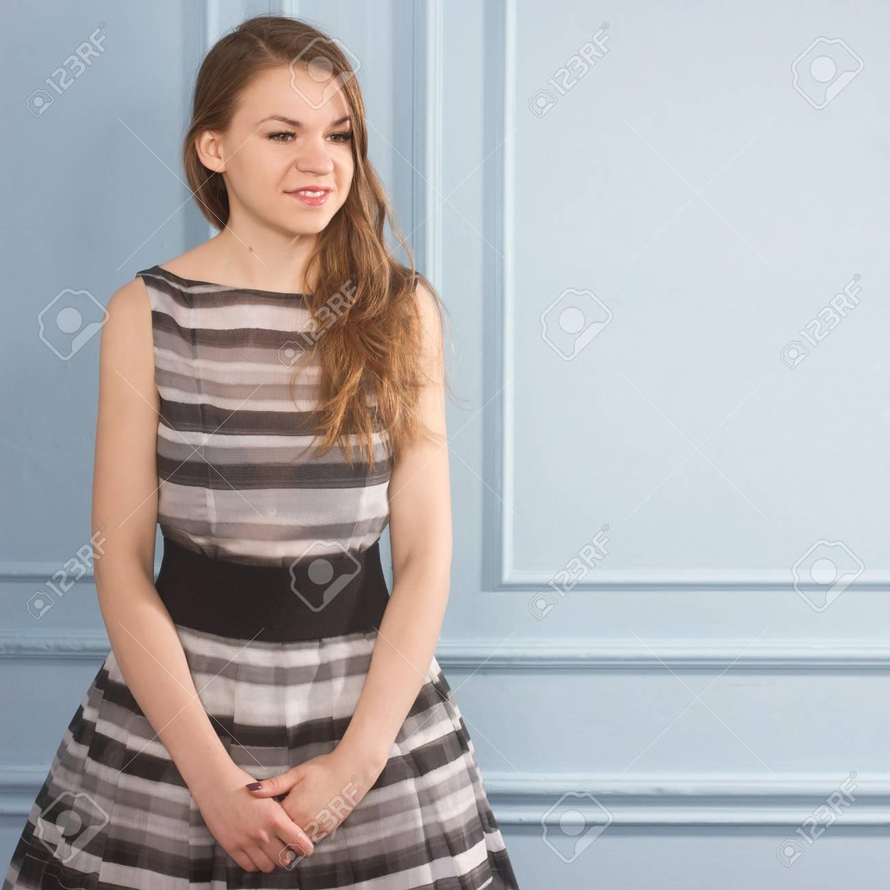 Schönes Mädchen In Einem Grauen Kleid In Der Nähe Einer Blauen Wand ...
