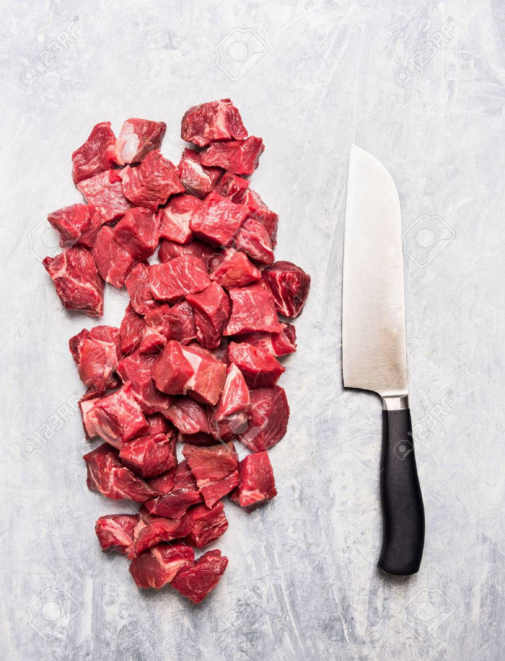 Raw Beef Goulash Meat Diced For Stew With Meat Knife On Light Gray Wooden Background Top