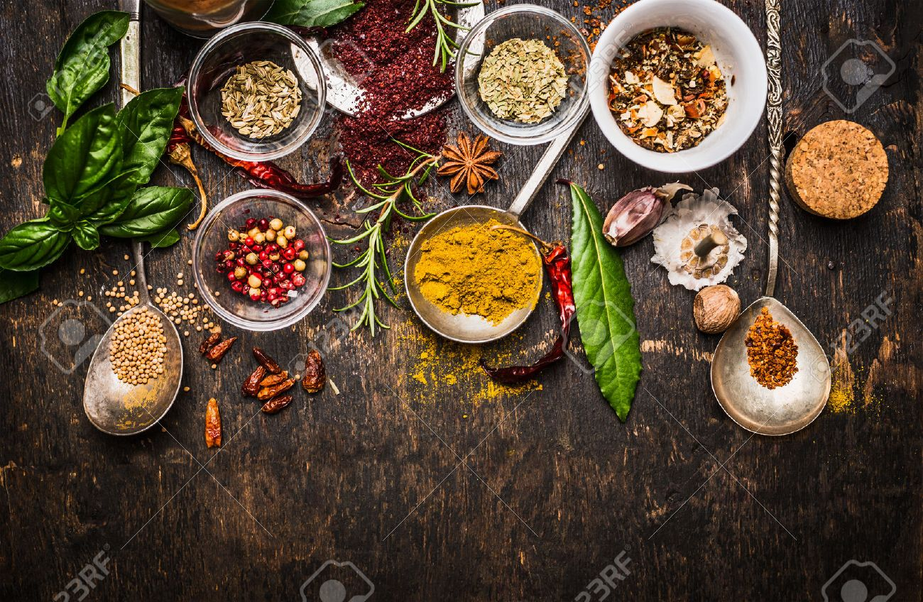 Dry colorful spices in spoons and bowls with fresh seasoning on dark rustic wooden background, top view, border - 45656350