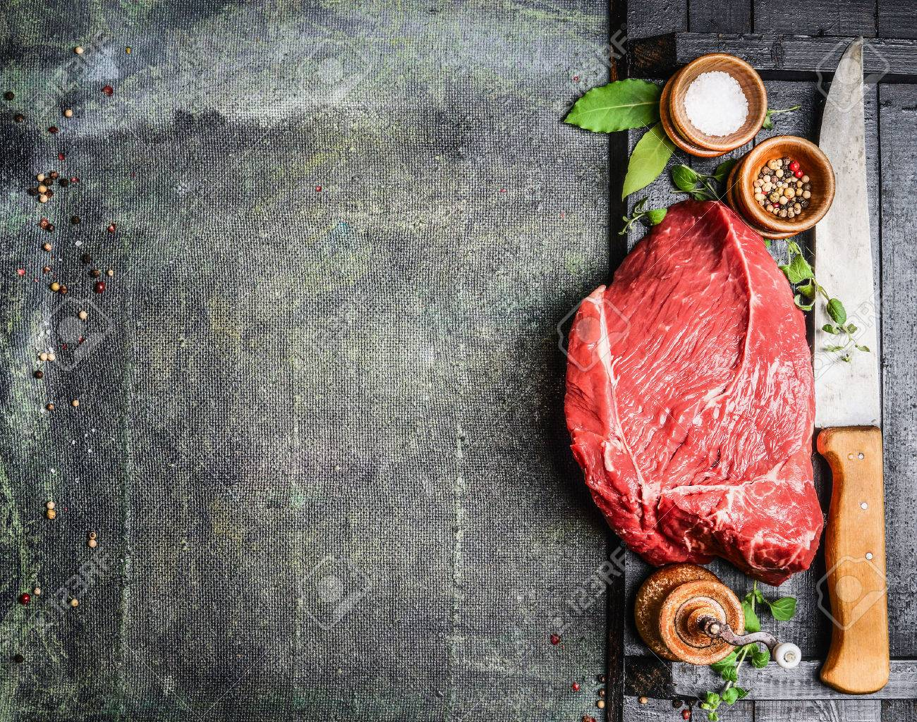 Fresh raw meat with herbs,spices and butcher knife on rustic background, top view, place for text. Cooking concept. Horizontal. - 50916097
