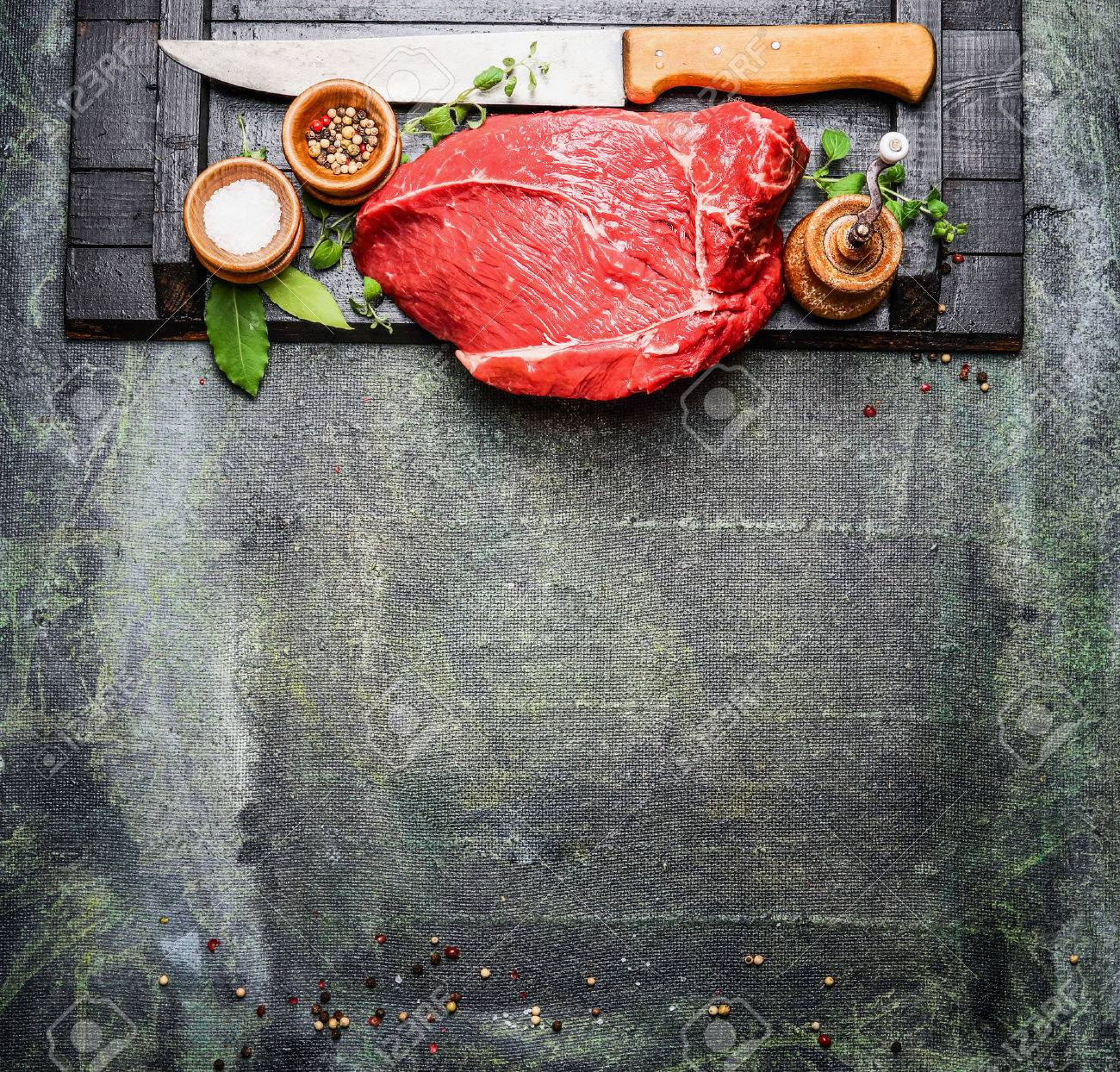 Fresh raw meat with cooking seasoning and butcher knife on rustic background, top view. - 50916258