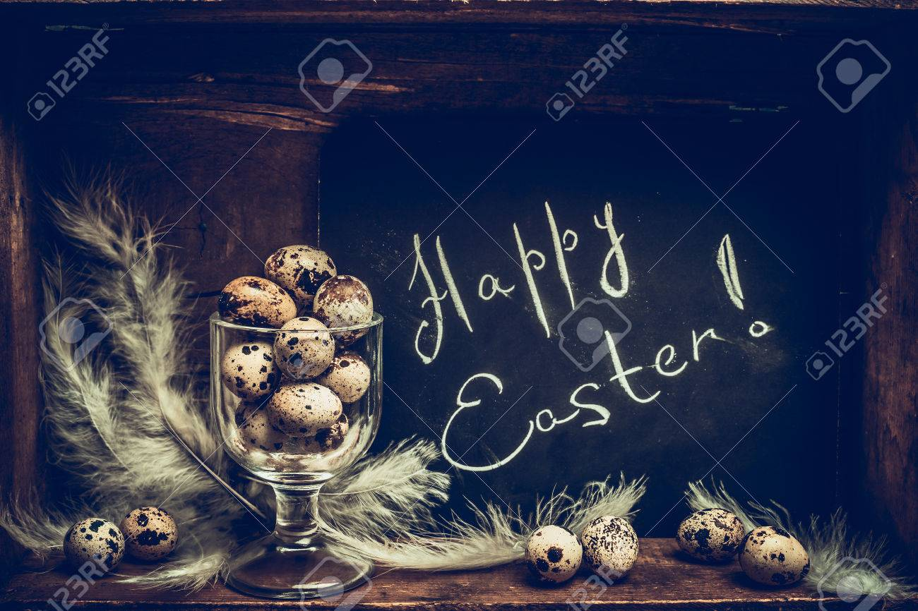 Happy Easter Greeting Card With Quail Eggs In Glass And Chalkboard Over Rustic Wooden Background