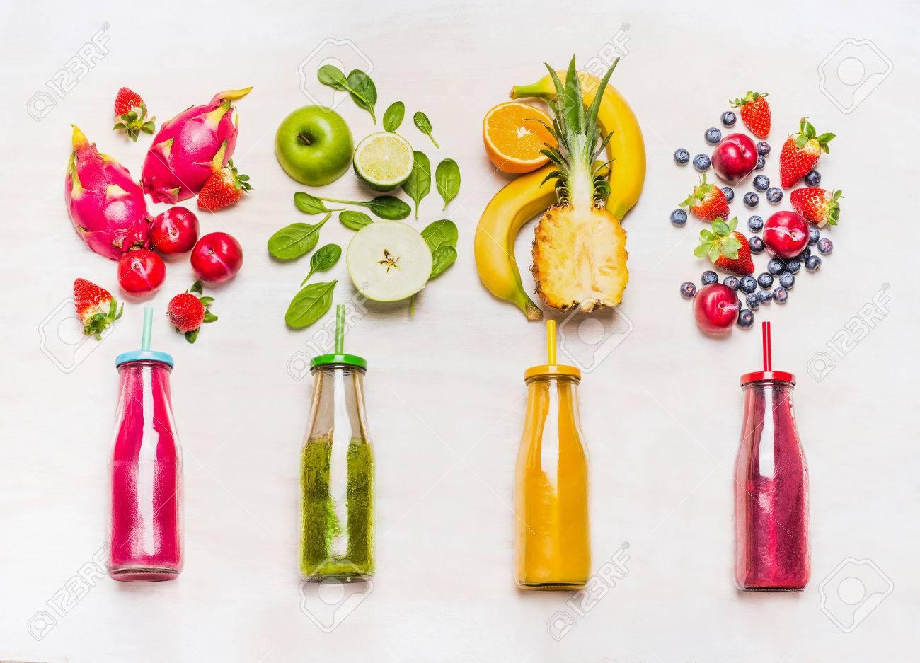surtido de batidos de frutas y verduras en botellas de vidrio con la paja en el