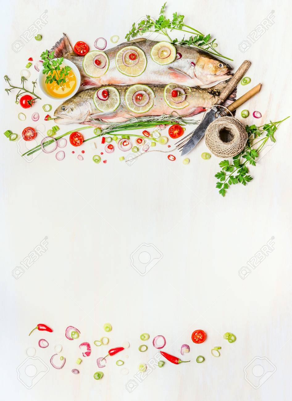 Fish food background with raw whole Fish , fresh delicious cooking ingredients and cutlery on white wooden , top view, frame. Healthy food or diet concept. Fish dishes. - 54155040