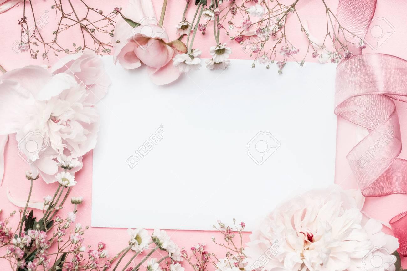 Carte vierge blanche avec des fleurs en pastel et un ruban sur fond pâle  rose, cadre floral. Concept de salutation créative, invitation et vacances