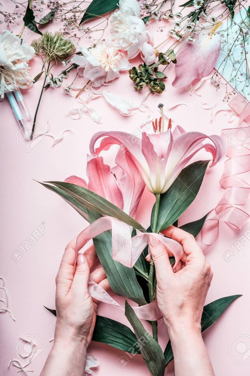 Female Hands Making Lovely Pink Lily Flowers Bouquet On Pastel