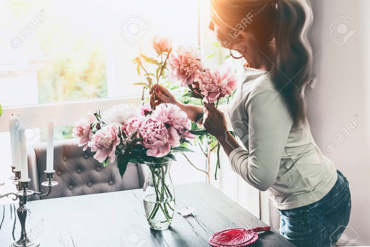 Attractive women arranging peonies bunch in glass vase on table at window  in living room. bd0e54ea12