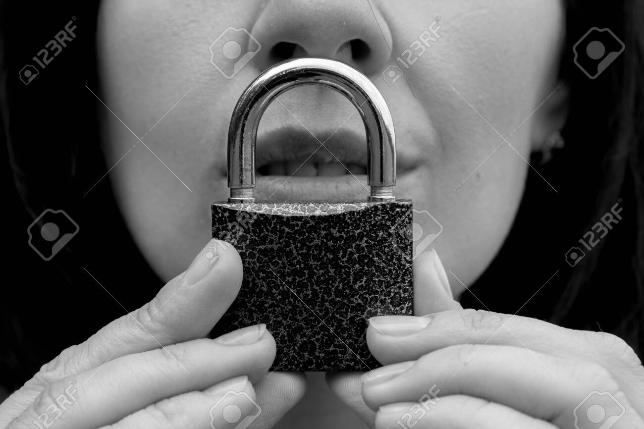 Conceptual portrait of a woman keeping silence with lock over her mouth. caucasian woman keep mouth locked. Language barrier concept and protecting the rights of women. Black and white. - 129085952