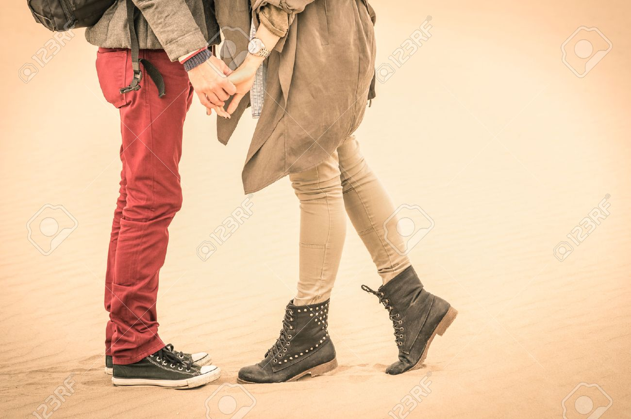 Concept of love in autumn - Couple of young lovers kissing outdoors with closeup on legs and shoes - Desaturated nostalgic filtered look Stock Photo - 32112347