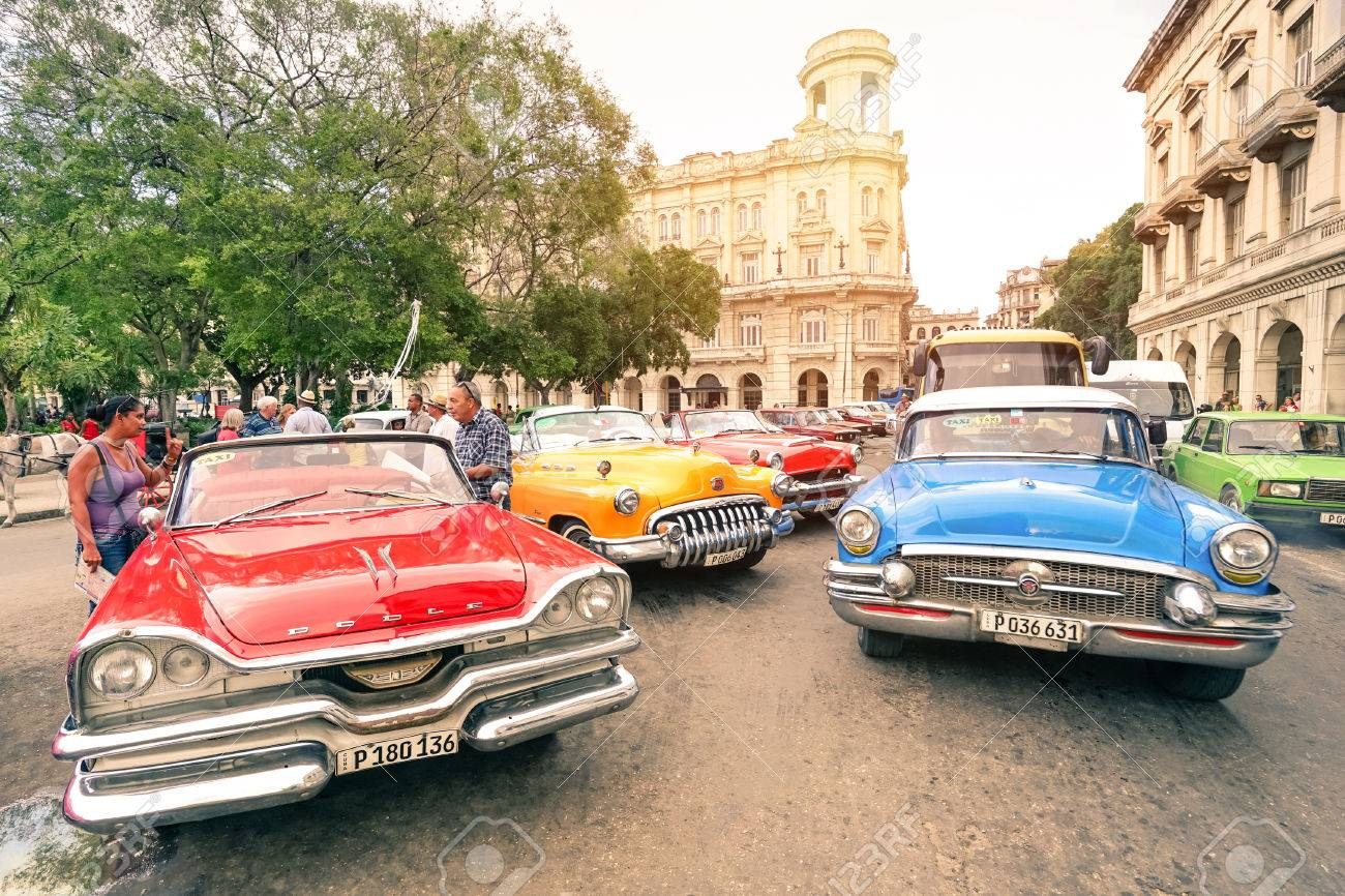 HAVANA, CUBA - NOVEMBER 17, 2015: multicolored vintage american cars in Havana City with National Museum of Fine Arts - Warm afternoon color tones with sunshine halo - 50730988