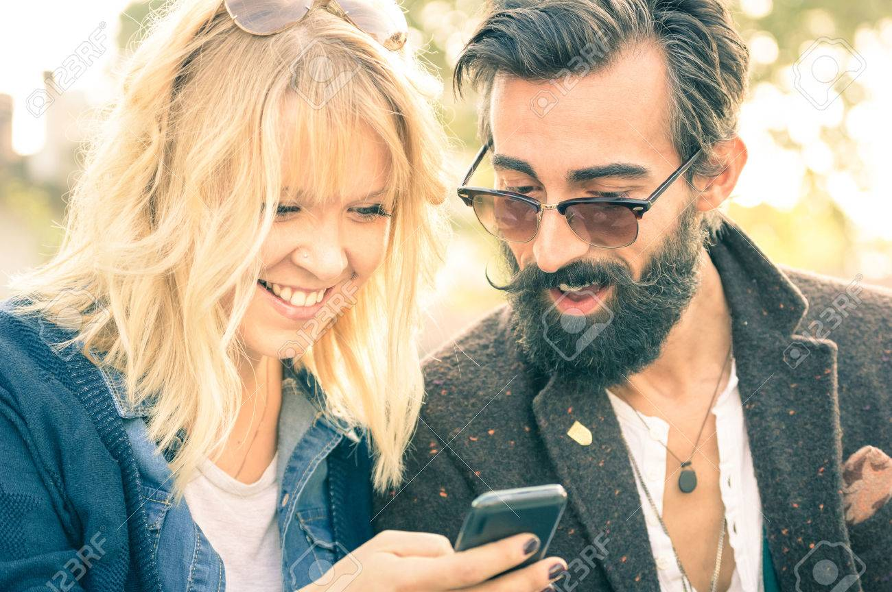 Happy young couple with vintage clothes having fun with smartphone - Beginning of love story with hipster best friends on mobile phone - Addiction concept with new technology - Shallow depth of field - 53023662