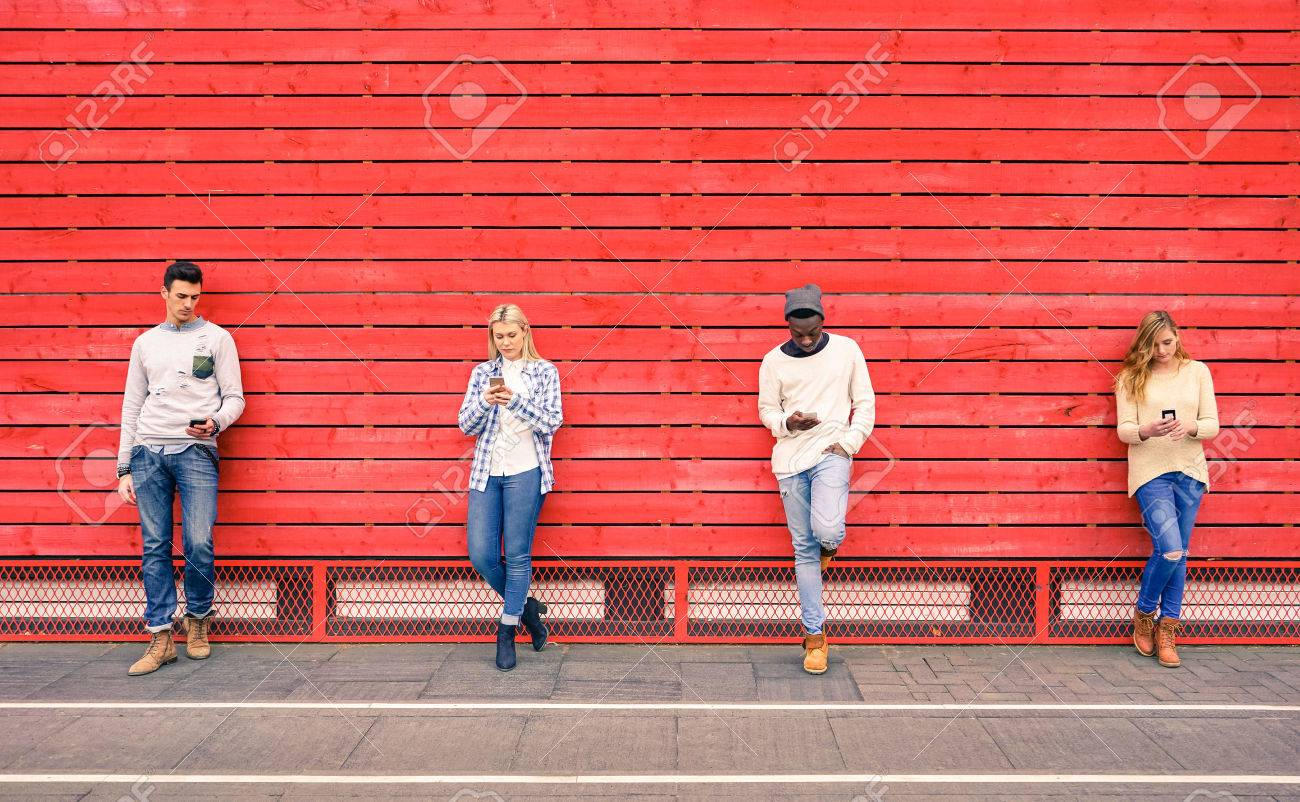 Group of multiracial fashion friends using smartphone with red wood background - Technology addiction in urban lifestyle with disinterest towards each other - Addicted people to modern mobile phones - 54114006