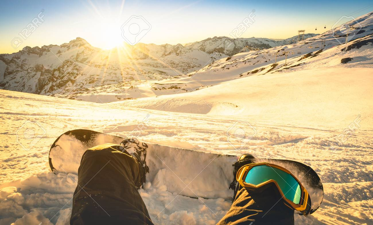 Snowboarder sitting on relax moment at sunset in Les Deux Alpes ski resort - Winter sport concept with person on top of the mountain ready to ride down - Legs view point with warm backlighting filter - 67819477