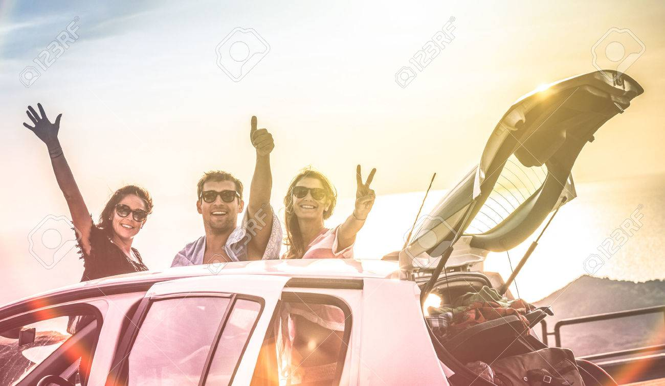 Group of best friends cheering on car road trip at sunset - Happy people outdoor on vacation tour adventure - Friendship concept at travel together around world - Soft focus with vintage color filter - 72773011