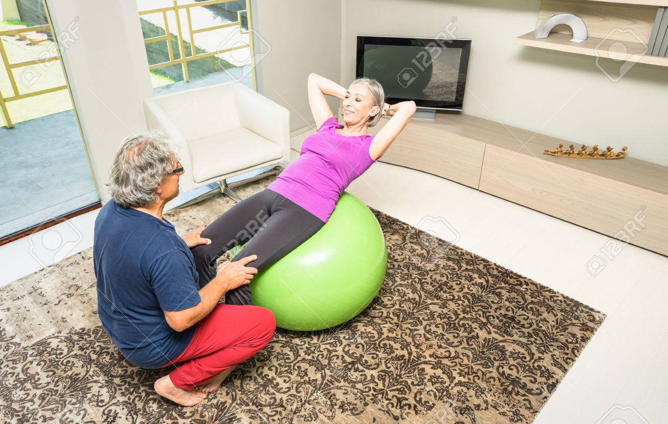 Active elderly couple training with swiss ball at home retired