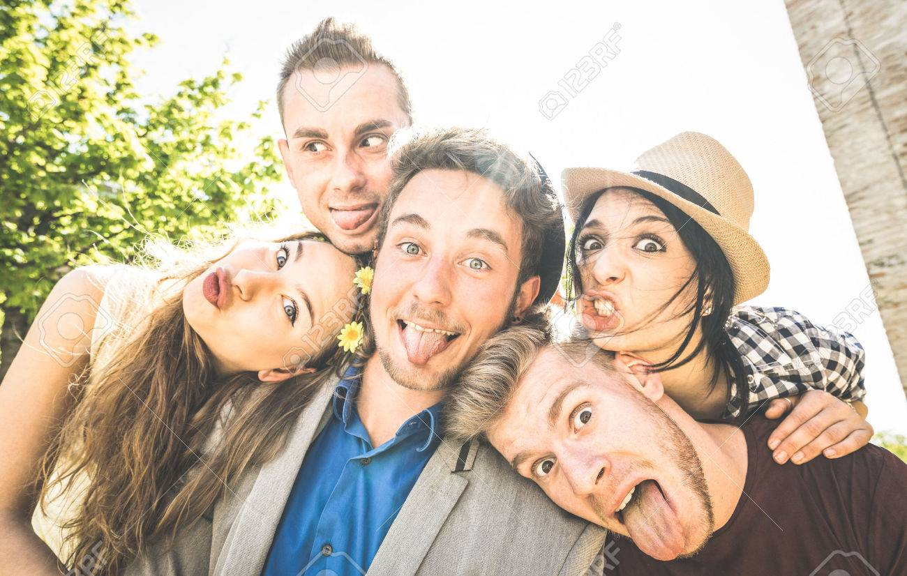 Group of best friends taking selfie outdoor with back lighting - Happy concept with young people having fun together - Cheer and friendship at city tour - Retro vintage filter with focus on middle guy - 75689822