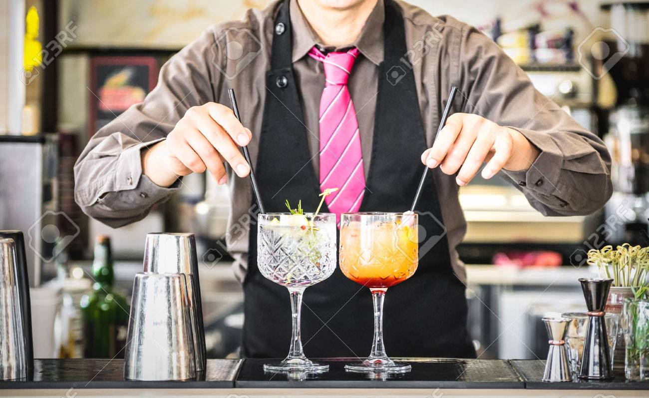 Classic bartender serving gin tonic and tequila sunrise with straw on drink glasses cups at fashion cocktail bar - Food and beverage concept with professional barman working at mixology restaurant - 79331446