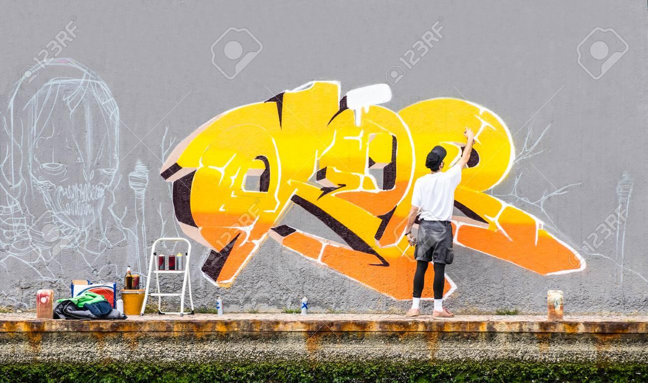 Street artiste peinture graffiti coloré sur le mur de l\'espace public -  concept d\'art moderne de type urbain effectuant et en préparant la peinture  ...