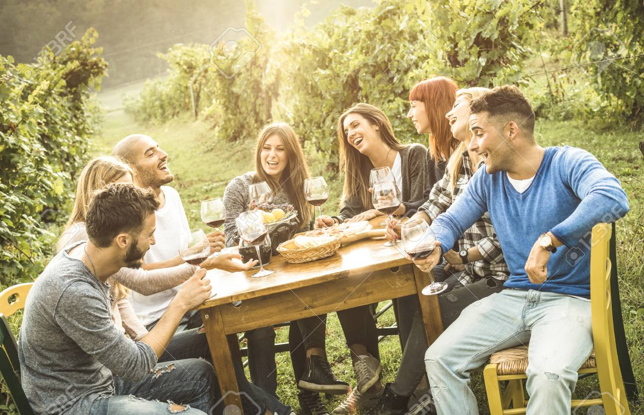 Happy friends having fun outdoor drinking red wine - Young people eating food at harvest time in farmhouse vineyard winery - Youth friendship concept with shallow depth of field - Warm contrast filter - 88799579