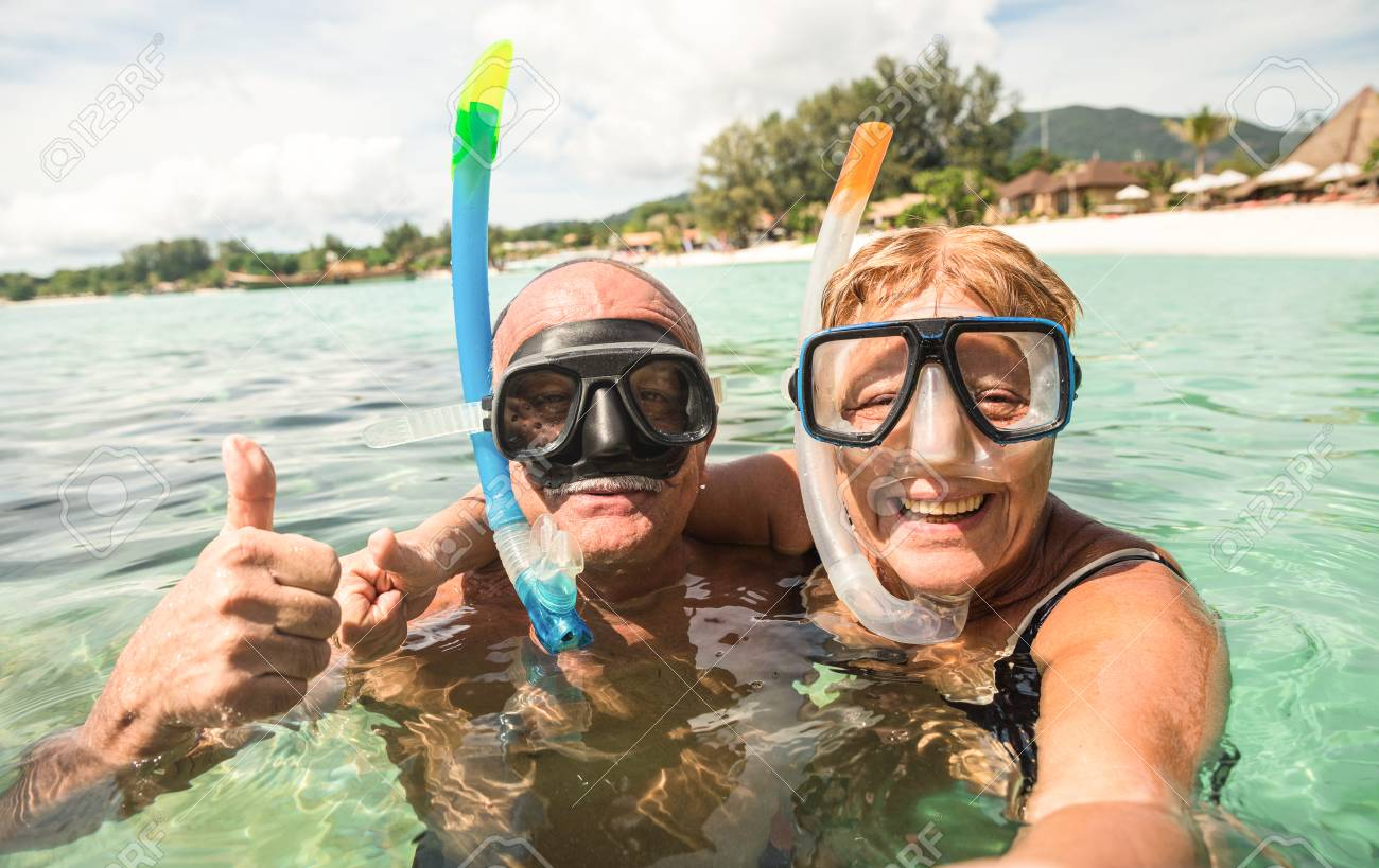 Senior happy couple taking selfie in tropical sea excursion with water camera - Boat trip snorkeling in exotic scenarios - Active retired elderly and fun concept around the world - Warm bright filter - 89504405