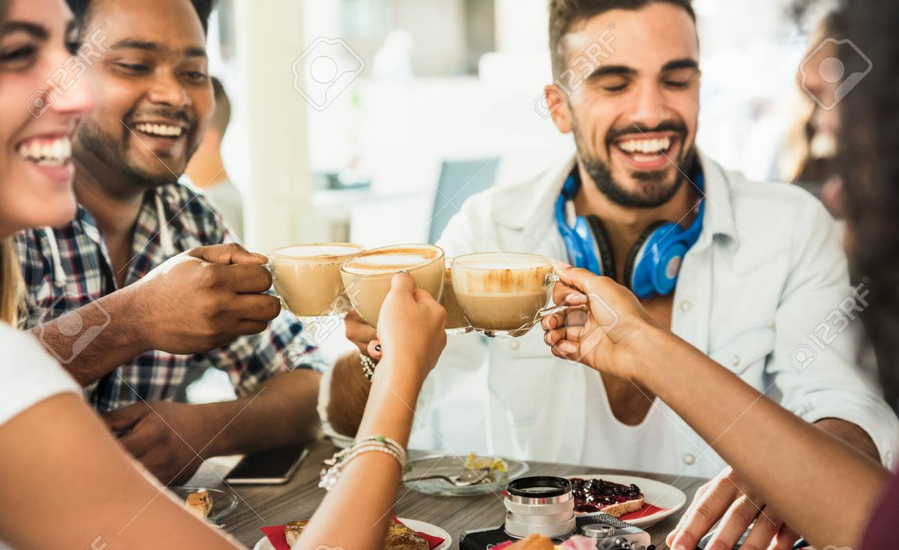 Friends group drinking latte at coffee bar restaurant - People talking and having fun together at fashion cafeteria - Friendship concept with happy men and women at cafe - Focus on cappuccino cups - 94723494