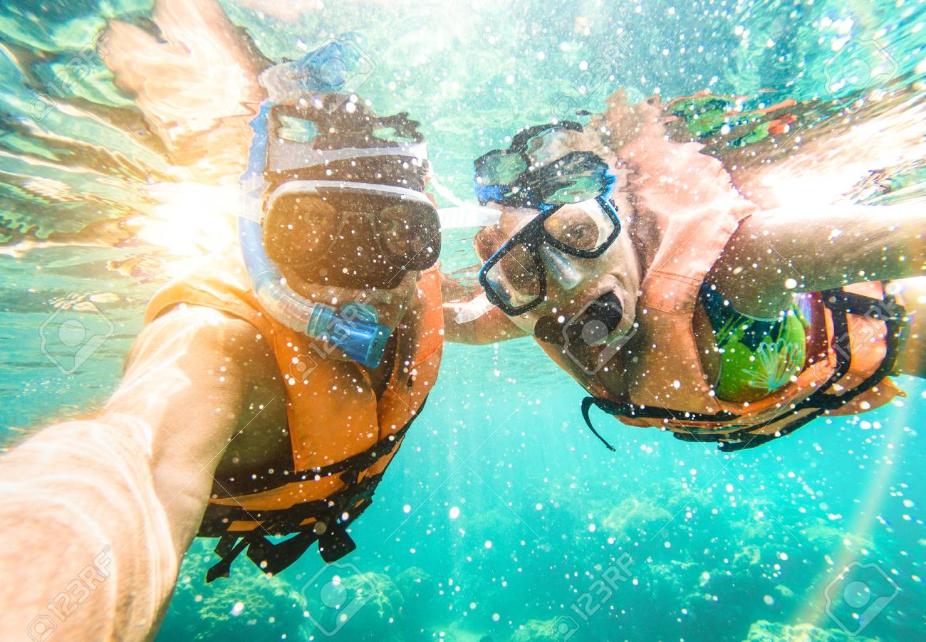 Senior happy couple taking selfie in tropical sea excursion with water camera - Boat trip snorkeling in exotic scenarios - Active retired elderly and fun concept on scuba diving - Warm vivid filter - 96392392