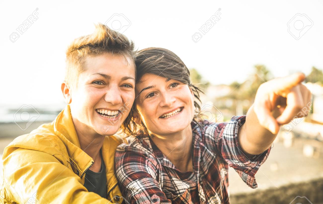 Happy girlfriends in love sharing time together at travel trip pointing on horizon - Women friendship concept with girls couple having fun on fashion clothes outdoors - Bright warm sunset filter - 96372823