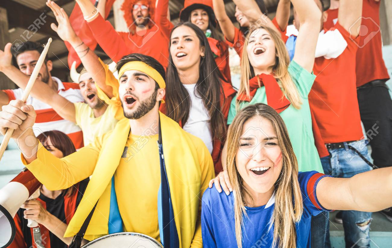 Young football supporter friends cheering and watching soccer cup match at intenational stadium - People fans group with multicolored t-shirts having excited fun on sport world championship concept - 100182987