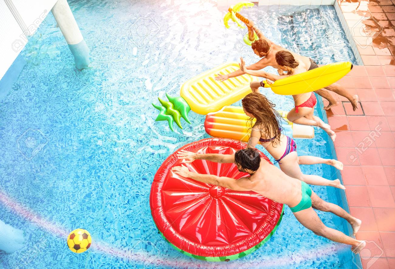 Top view of active friends jumping at swimming pool party - Vacation..