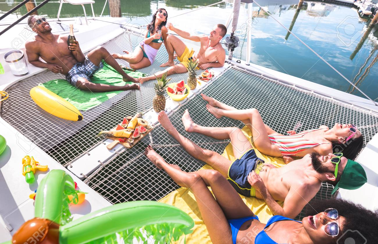 Multiracial happy friends having relax fun at sail boat party - Friendship concept with multi racial people on catamaran sailboat - Luxury travel and exclusive vacation concept - Vivid bright filter - 123656480
