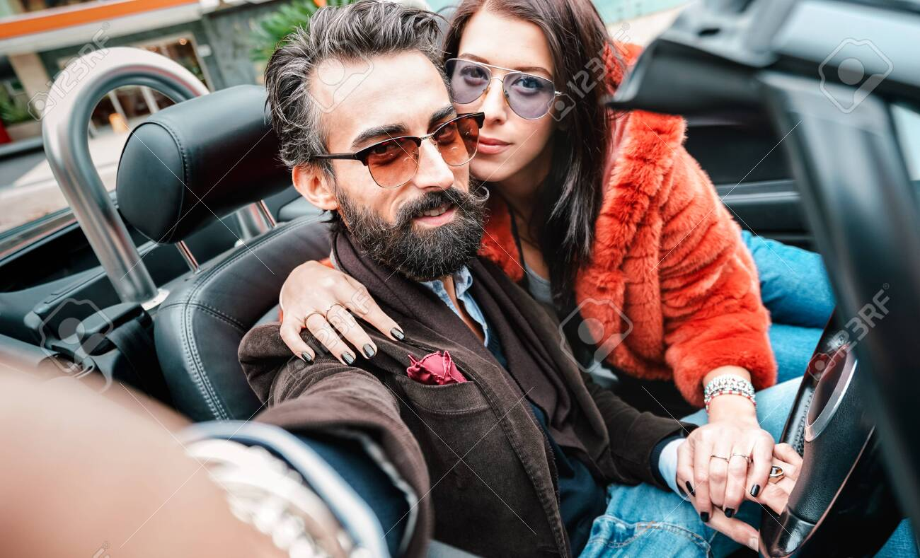 Cool happy couple taking selfie at roadster car trip - Bearded man with beautiful woman having fun on roadtrip experience - Luxury concept with people traveling together - Focus on face of hipster guy - 138163419
